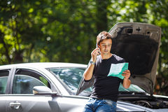 Handsome young man calling for assistance. With his car broken down by the roadside Royalty Free Stock Image