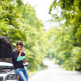 Handsome young man calling for assistance. With his car broken down by the roadside Stock Photography