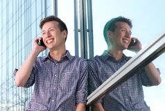Handsome young man calling on mobile phone outdoors Stock Images