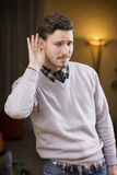 Handsome young man can't hear, putting hand around his ear. Indoors shot inside a house Stock Image