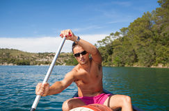 Handsome young man on a canoe on a lake, paddling Royalty Free Stock Photos