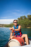 Handsome young man on a canoe on a lake, paddling Stock Image