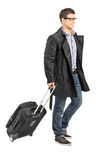 Handsome young man carrying his luggage Royalty Free Stock Photography