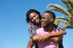 Handsome young man carrying woman on his back outdoors Stock Photography