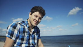 Handsome young man in casual checkered shirt against bright beach background stock video footage