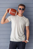 Handsome young man. In casual clothes and sun glasses is holding an American football ball, looking at camera and smiling, standing against gray wall Royalty Free Stock Images