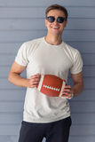 Handsome young man. In casual clothes and sun glasses is holding an American football ball, looking at camera and smiling, standing against gray wall Stock Photography