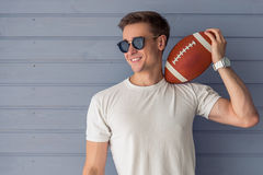 Handsome young man. In casual clothes and sun glasses is holding an American football ball and smiling, standing against gray wall Royalty Free Stock Photography