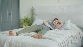 Handsome young man jumping in bed then lying relaxing smiling in bedroom. Handsome young man in casual clothing is jumping in double bed then lying relaxing stock footage