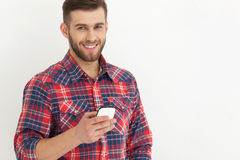 Handsome young man in casual wear typing text message. Typing text message. Portrait of handsome young man in casual wear holding mobile phone against white Royalty Free Stock Photos