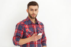 Handsome young man in casual wear typing text message. Typing text message.Portrait of handsome young man in casual wear holding mobile phone against white wall Stock Photos