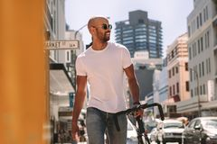 Handsome man in casuals walking outdoors with bicycle. Handsome young man in casuals walking down the street with a bicycle. African man in casuals walking royalty free stock photos