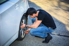 Handsome Young Man Changing Tires of his Car. Handsome Young Man in Casual Clothing Squatting Besides the Wheel of a his White Car Changing Tires Stock Images