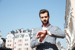 Handsome young man checking the time on his wrist watch Royalty Free Stock Photography