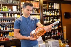 Handsome young man choosing fine wines stock image
