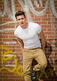 Handsome young man on city brick wall Stock Image