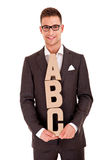 Handsome young man in classic suit and with letters abc Stock Image