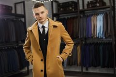 Handsome man stands in suit shop fashionable rich male dressed in expensive clothes posing indoors stock photo