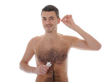 Handsome young man cleaning ears with cotton stick Royalty Free Stock Photo