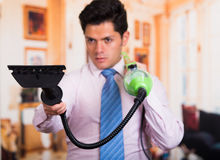 Handsome young Man cleaning home with vacuum cleaner in his shoulder Stock Photography