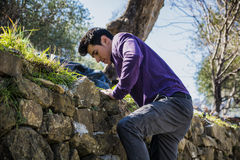 Handsome young man climbing stone wall Royalty Free Stock Photography