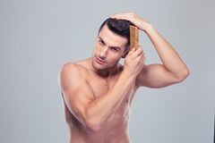 Handsome young man combing his hair Royalty Free Stock Photography