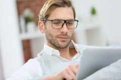 Handsome young man connected on tablet Stock Images