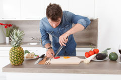 Handsome young man cooking in a modern kitchen. Royalty Free Stock Images