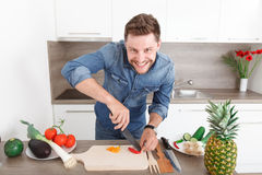Handsome young man cooking in a modern kitchen. Stock Image