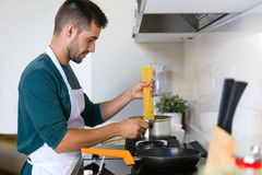 Handsome young man cooking pasta in the kitchen at home royalty free stock images