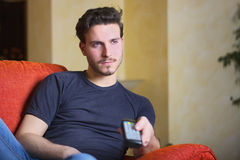 Handsome young man on counch, using TV remote control Royalty Free Stock Photography