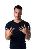 Handsome young man counting to eight with fingers and hands Stock Photos