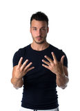 Handsome young man counting to nine with fingers and hands Stock Photos