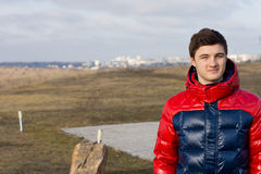 Handsome young man in the countryside. Handsome young man or teenager standing in a colourful winter jacket in the countryside with a town visible in the far Stock Images