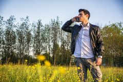 Handsome young man at countryside, using cell Royalty Free Stock Images