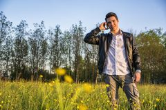 Handsome young man at countryside, using cell Royalty Free Stock Photos