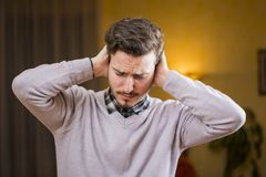 Handsome young man covering his ears, too much noise. Handsome young man covering his ears, stressed or unhappy because of too much noise. Indoors shot Royalty Free Stock Photography