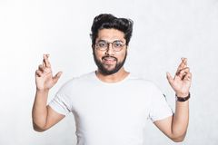 Handsome young man crosses fingers, anticipate hearing good news. Body language concept. Handsome young man crosses fingers, anticipate hearing good news. Body stock image