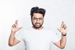 Handsome young man crosses fingers, closes eyes, anticipate hearing good news. Body language concept. Handsome young man crosses fingers, closes eyes stock photography