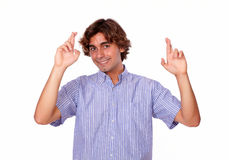 Handsome young man crossing fingers for luck Stock Photo