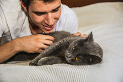 Handsome Young Man Cuddling his Gray Cat Pet Stock Images