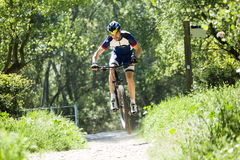 Handsome young man cycling in the mountain. Stock Photo
