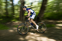 Handsome young man cycling in the mountain. Stock Images