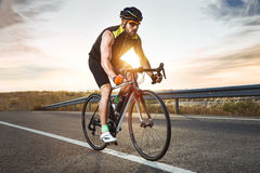 Handsome young man cycling on the road. Royalty Free Stock Images