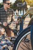 Handsome Young Man Cyclist Pumps Bicycle Wheel Maintenance Transport Concept Stock Photography