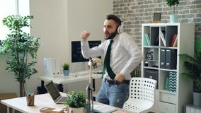 Handsome young man dancing listening to music in headphones in modern office