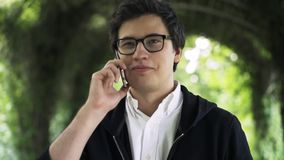 Young man in glasses is talking on his phone and walking in a park stock footage