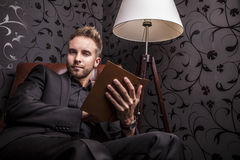 Handsome young man in dark suit with book relaxing on luxury sofa. Royalty Free Stock Photography