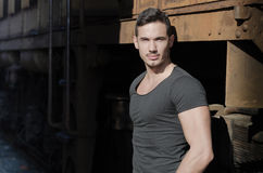 Handsome young man in dark t-shirt in front of old train Stock Image