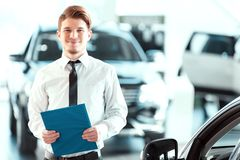 Handsome young man in dealership Stock Photography